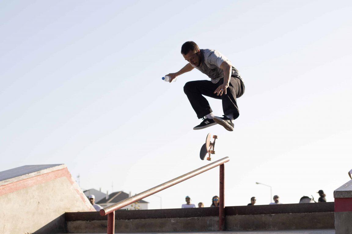 man wearing white t shirt performing skateboard tricks on rail under blue sky stockpack pexels scaled