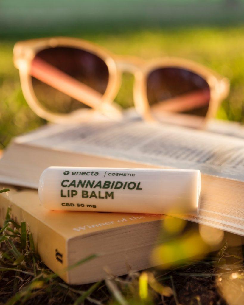 Cannabidiol lip balm on book on grass during daytime